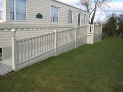 White hand rail on UPVC plastic deck with ramp