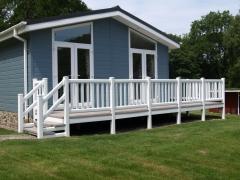 Holiday home deck white hand rail stone deck board caravan park lodge upvc plastic composite decking